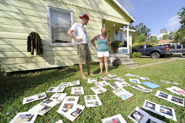Jarrod and Brandi Barlow view what remains of their children's photo album. Valentino Mauricio