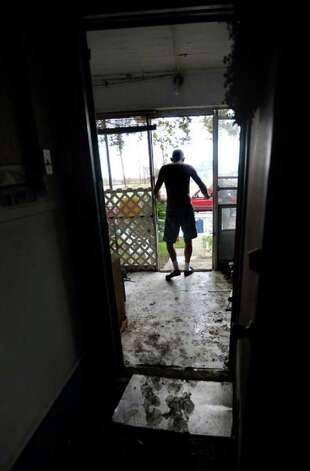 Paul Leonard checks flood damage to his  home in the historic district. Tammy McKinley