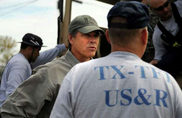 Governor Rick Perry discusses rescue and recovery efforts with members of the Texas Task Force. Tammy McKinley