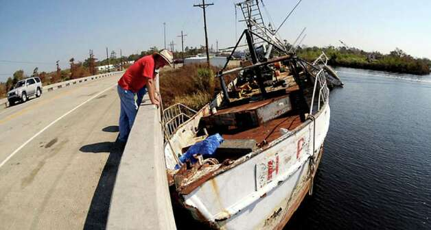 The force of Hurricane Ike lodged Bill Boiter's shrimp boat against the bridge crossing Adams Bayou. Tammy McKinley