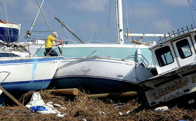 Don Miller tries to salvage what he can from his boat, the Bay Wind-O, at the Pleasure Island Marina. Tammy McKinley