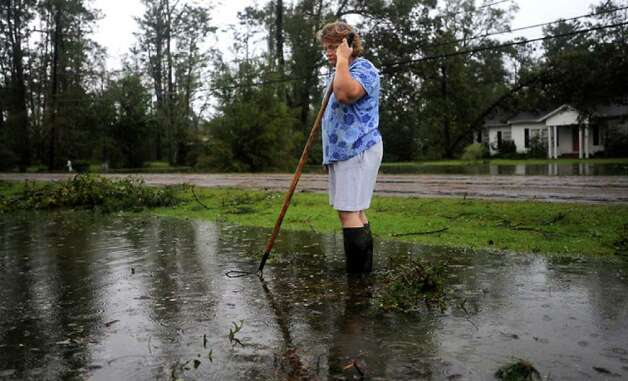Janice Bonura clears debris from a drainage ditch to keep water flowing and prevent rising water from flooding her home. Tammy McKinley