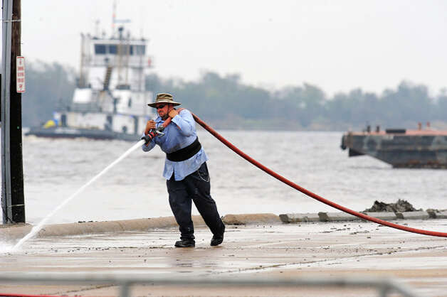 James Parks cleans mud from the driveway at Port Neches Park. Guiseppe Barranco