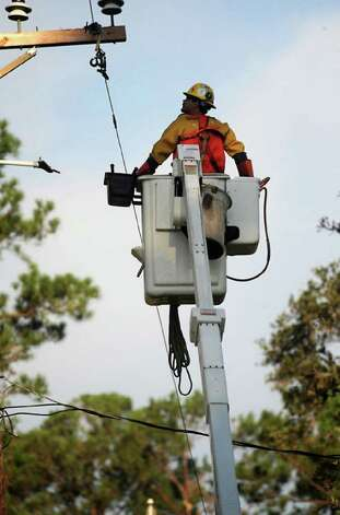 Jerry Gregg of Pike Electrical is lifted toward power lines in need of repair in the Bevil Oaks area. Tammy McKinley