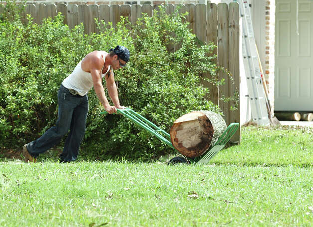 Nick Boulware with TLC Services hauls a portion of a tree trunk to the curb to be picked up by contract workers. Garbage pickup resumed within three to four days after the storm and debris pickup followed. Guiseppe Barranco