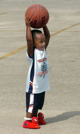 Raymond Chaisson, 2, bounces a basketball in the parking lot of the Beaumont Municipal Athletic Complex  after returning with his family from evacuation to Tyler. Pete Churton