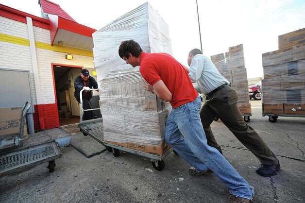 From left, Fernando Molaes, Logan Chilek and Cody Castillo push food supplies into the back of McDonald's near Parkdale Mall before reopening for the first time following the hurricane. Guiseppe Barranco