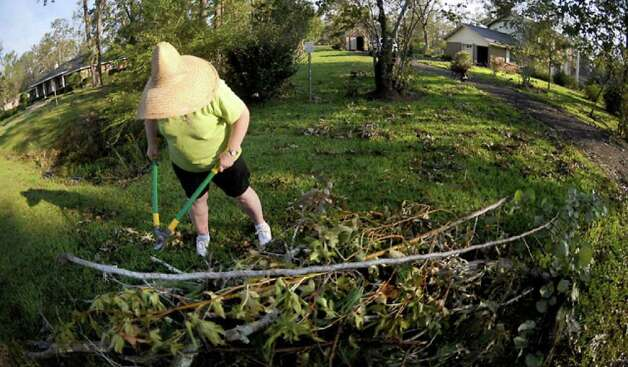 Olga Netterfield cuts fallen branches in her yard into manageable pieces. Virtually no homes in the storm-affected area escaped downed tree limbs and other debris scattered by hurricane-force winds. Tammy McKinley
