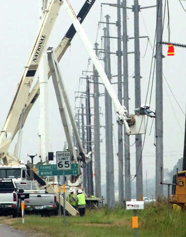 Crews repair damaged utility poles on Texas 124 just outside of the Beaumont city limits. Pete Churton