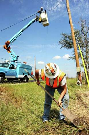 Curtis Quintana and Angel Lara of Windstream Telephone work to repair lines. Tammy McKinley