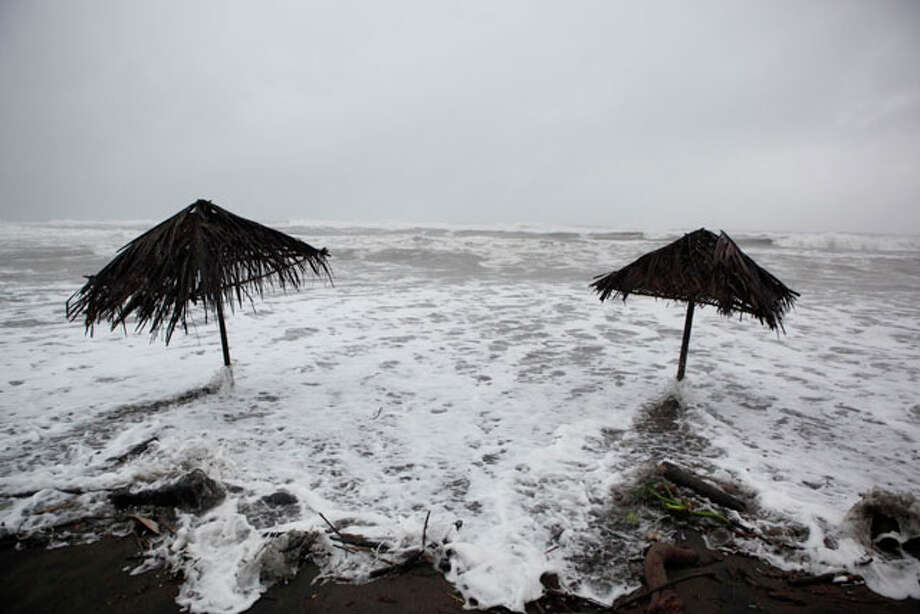 Sea waves hit sunshades at Maracaibo beach in Nautla, in the state of Veracruz, Mexico, on Friday. Hurricane Karl reached Category 3 strength in the Gulf of Mexico and is expected to reach the country's central coast Friday. / AP