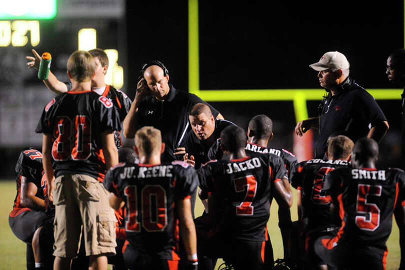 Kirbyville coaches talk with players during a timeout against Bridge City. Friday, September 17, 201