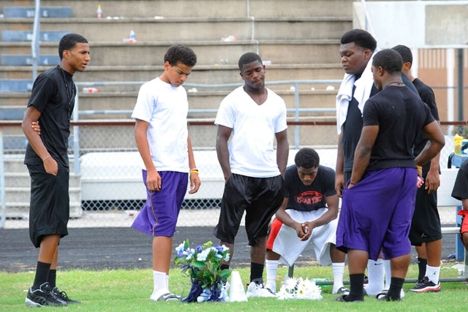West Orange-Stark High School teammates of Reggie Garrett, the quarterback who died after collapsing on the sidelines during Friday's game, visit a memorial placed at the spot where Garrett fell at the Mustangs' stadium. Saturday, September 19, 2010  Valentino Mauricio/The Enterprise / Beaumont