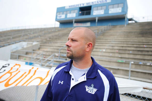 Assistant WO-S coach Toby Foreman looks toward the center of the football field where he watched the sun come up Saturday. After daybreak, he saw someone place twenty white roses on the 50-yard line at the Mustangs' stadium Saturday in memory of quarterback Reggie Garrett, who collapsed on the sidelines and died during a game Friday night. Saturday, September 19, 2010  Valentino Mauricio/The Enterprise / Beaumont