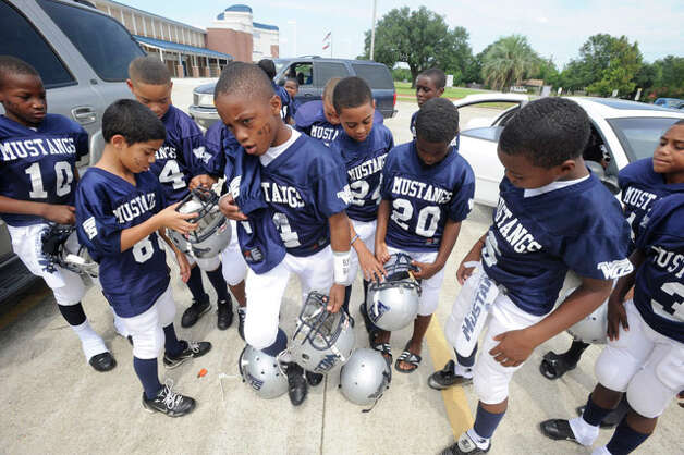 On Saturday in memory of fallen West Orange-Stark quarterback Reggie Garrett, the Junior Mustangs, ages 8 to 10, gathered at West Orange-Stark High School Saturday afternoon to travel to their game at Port Neches. They wrote Garrett's number, 12, on their taped wrists and faces and dedicated the game to him.  Saturday, September 18, 2010. Valentino Mauricio/The Enterprise