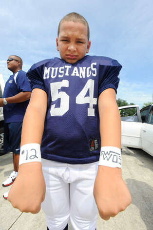 Jr. Little Mustangs player Keontae Spears, 8, displays the number 12 on his wrist in memory of fallen West Orange-Stark quarterback Reggie Garrett before the Little Mustangs play Port Neches-Groves on Saturday. The Jr. Little Mustangs all wore the number 12 in honor of Garrett. Saturday, September 19, 2010  Valentino Mauricio/The Enterprise / Beaumont