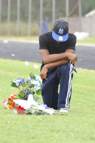 West Orange-Stark High School student Jhayllen Monnete visits a memorial placed at the spot where West Orange-Stark High School quarterback Reggie Garrett  died after collapsing on the sidelines during Friday's game in West Orange, Texas.   Saturday, September 19, 2010  (AP Photo/Beaumont Enterprise Valentino Mauricio) / Beaumont