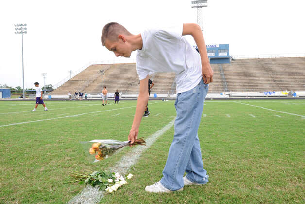 West Orange-Stark graduate Toren Swift places a bouquet of roses on the midfield 50-yard line at the Mustangs stadium Saturday in memory of quarterback Reggie Garrett, who collapsed on the sidelines and died during a game Friday night. Swift who attended the memorial with his father, Toren Swift Sr., said he grew up with Garrett playing basketball as neighbors. Saturday, September 19, 2010  Valentino Mauricio/The Enterprise / Beaumont