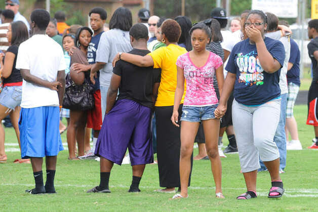West Orange-Stark High School students comfort each other during a student memorial at Dan Hooks Stadium for Reggie Garrett, the WO-S quarterback who died after collapsing on the sidelines during Friday's game in West Orange, Texas.  Saturday, September 19, 2010  (AP Photo/Beaumont Enterprise Valentino Mauricio) / Beaumont