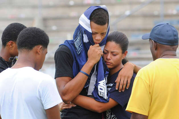 West Orange-Stark wide receiver Mark Roberts, center, is comforted by friends and classmates at Dan Hooks Stadium on Saturday during a memorial for teammate, quarterback Reggie Garrett, who collapsed on the sidelines and died during a game Friday night in West Orange, Texas. Roberts caught the touchdown pass that Garrett threw before collapsing on Friday night. Saturday, September 19, 2010  Valentino Mauricio/The Enterprise