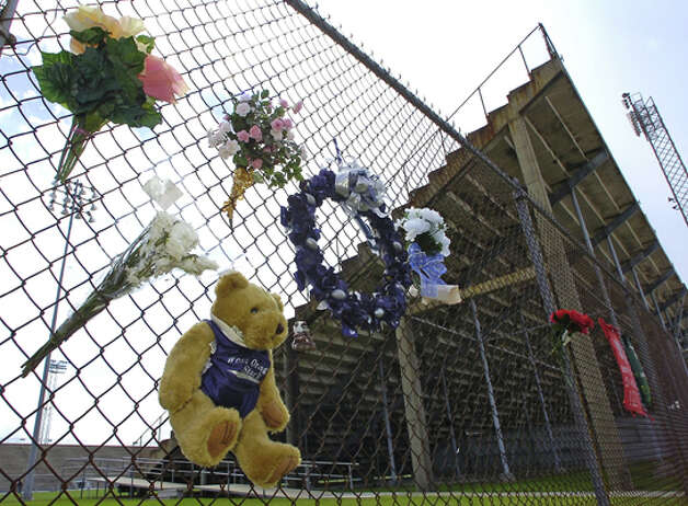 Flowers, wreaths, jerseys with messages, and even a stuffed bear hang on the fence outside the Dan R Hooks football stadium Monday afternoon, where WO-S quarterback Reggie Garrett collapsed  Friday night during a game with Jasper.   Dave Ryan/The Enterprise