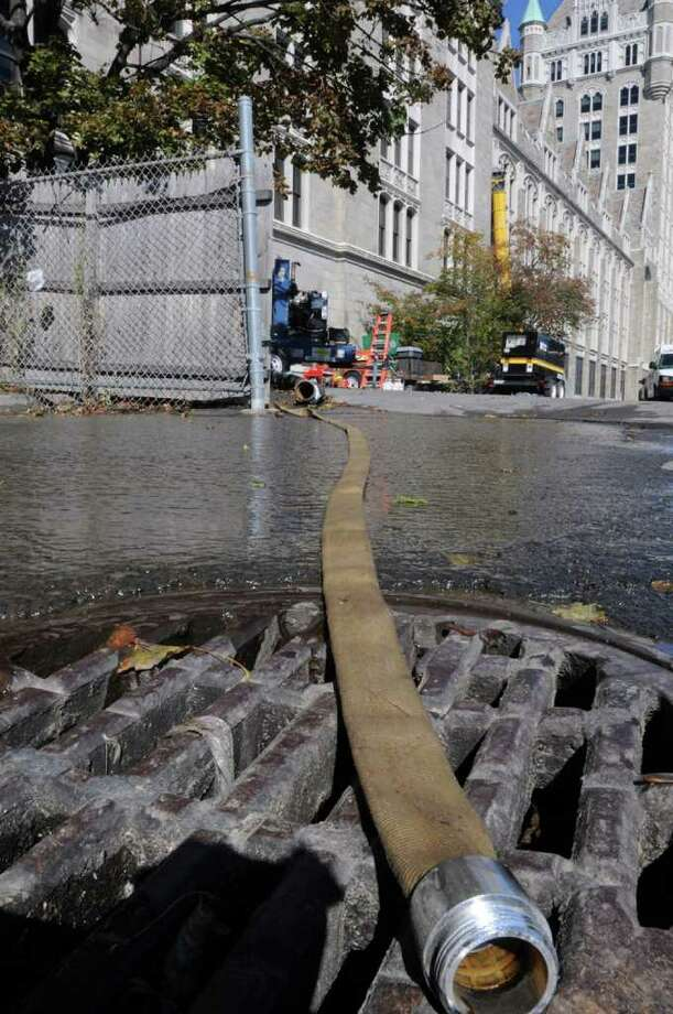 Water is pumped out of the SUNY headquarters building in Albany on October 12, 2010.  Hundreds of workers have been told not to report to work because of a major water emergency that knocked out the power, computers and telephone systems. (Lori Van Buren / Times Union) Photo: Lori Van Buren
