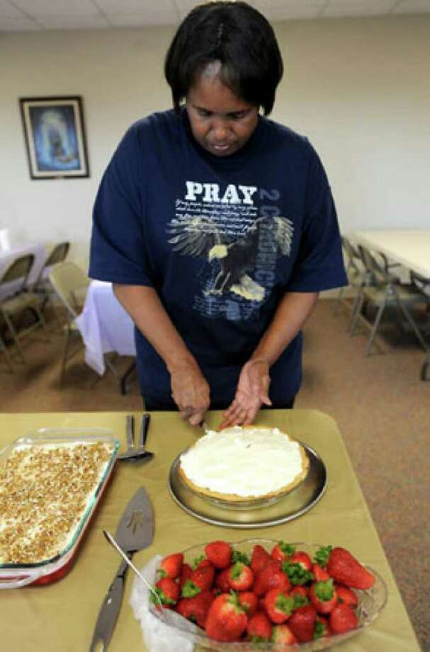 Charlene Lewis slices pie before the community fellowship pot luck sponsored by the Methodist Church at the First Baptist Church in Sabine Pass, Tuesday. Before Hurricane Rita devastated the area, there were five churches in Sabine Pass. Since Hurricane Ike rolled through, only 2 remain. Several churches are sharing the First Baptist Church's facilities for fellowship and worship as they wait for their facilities to be rebuilt. Tammy McKinley/The Enterprise / Beaumont