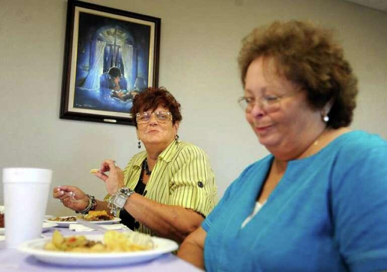 Lois Berg and Betty Adkins joke around during the Methodist Church's community fellowship pot luck g