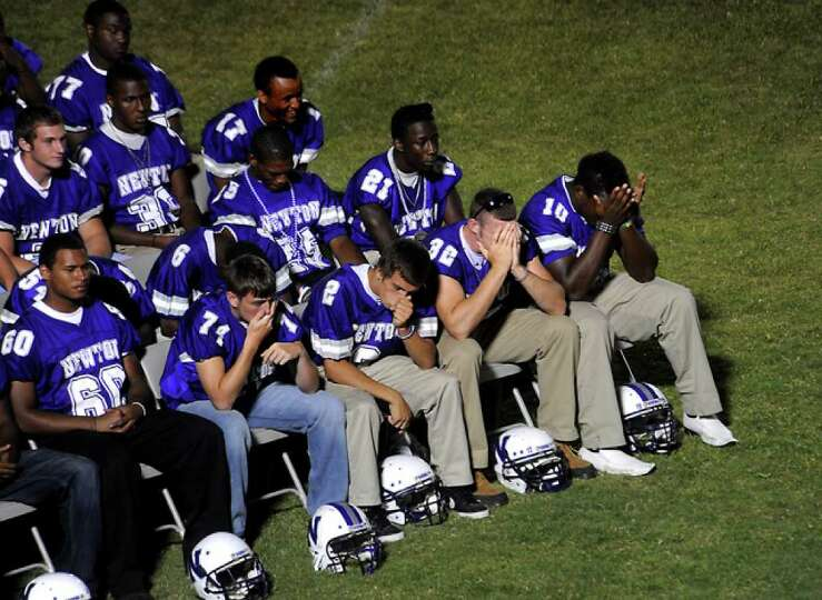 The 2010 Newton football team listen to Reverend Jason Fortenberry as hundreds of friends, family an