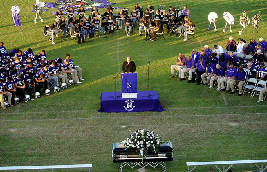 Father Ron Foshage offers the Invocation as hundreds of friends, family and fans gather together to honor the life and pay final respects to Coach Curtis Barbay during a public memorial service in his honor at Newton High School in Newton, Tuesday. Tammy McKinley/The Enterprise / Beaumont Enterprise