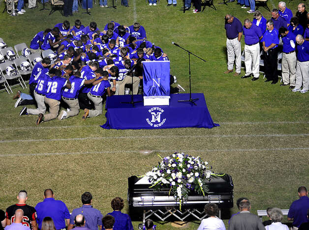 The 2010 Newton football team kneel down to say the Lord's Prayer as hundreds of friends, family and fans gather together to honor the life and pay final respects to Coach Curtis Barbay during a public memorial service in his honor at Newton High School in Newton, Tuesday. Tammy McKinley/The Enterprise / Beaumont