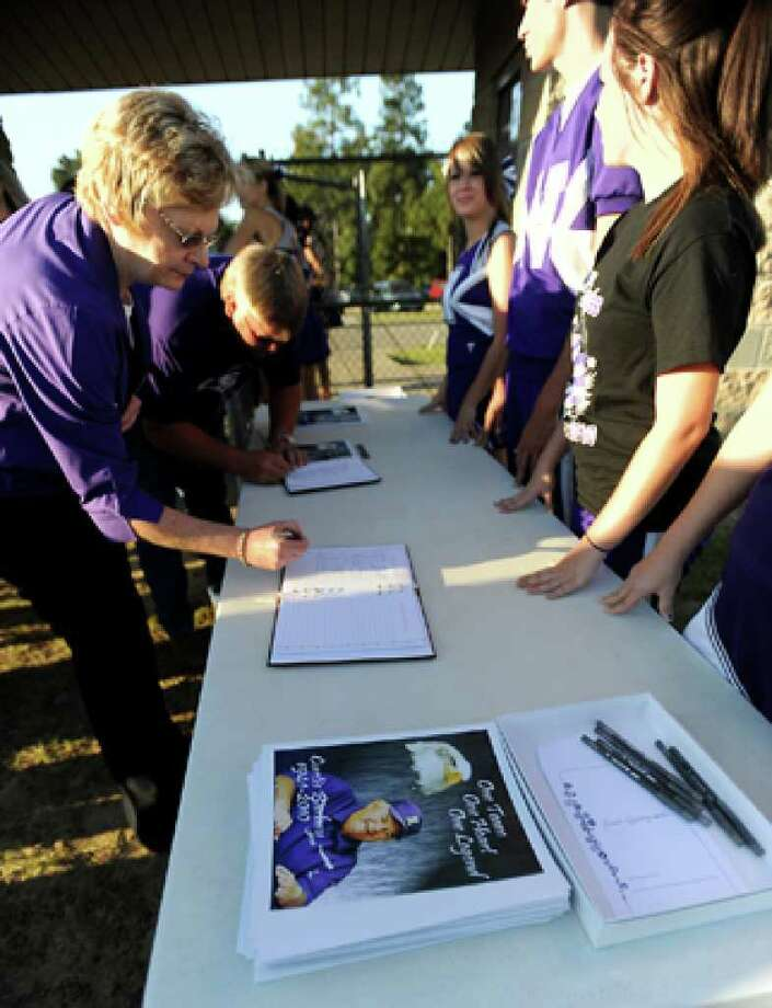 Hundreds of friends, family and fans sign the guest books as they gather together to honor the life and pay final respects to Coach Curtis Barbay during a public memorial service in his honor at Newton High School in Newton, Tuesday. Tammy McKinley/The Enterprise / Beaumont Enterprise