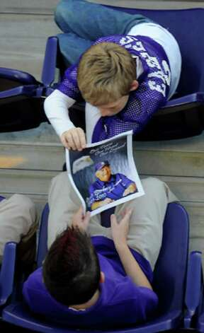 Two young men look over the program as hundreds of friends, family and fans gather together to honor the life and pay final respects to Coach Curtis Barbay during a public memorial service in his honor at Newton High School in Newton, Tuesday. Tammy McKinley/The Enterprise / Beaumont Enterprise