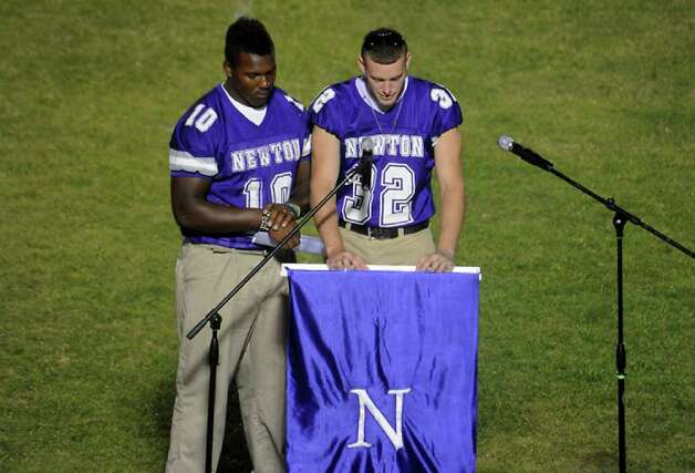 Krishon Seastrunk and Evan Fuller of the 2010 team offer rememberances as hundreds of friends, family and fans gather together to honor the life and pay final respects to Coach Curtis Barbay during a public memorial service in his honor at Newton High School in Newton, Tuesday. Tammy McKinley/The Enterprise / Beaumont Enterprise