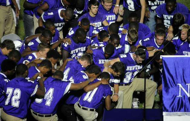 The 2010 Newton football team kneel down to say the Lord's Prayer as hundreds of friends, family and fans gather together to honor the life and pay final respects to Coach Curtis Barbay during a public memorial service in his honor at Newton High School in Newton, Tuesday. Tammy McKinley/The Enterprise / Beaumont Enterprise