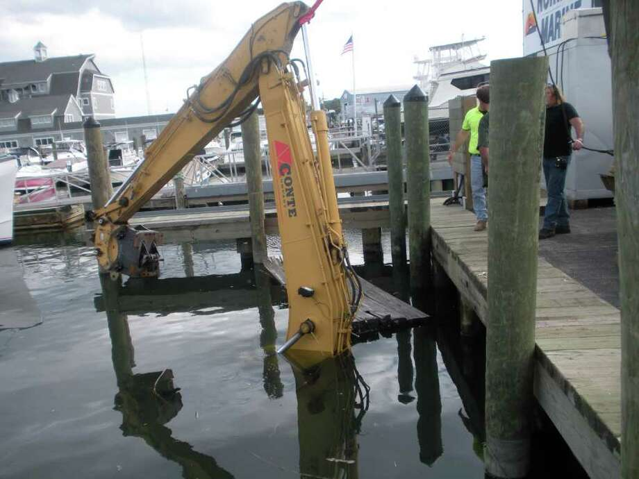 A backhoe fell off the dock at Norwest Marine on Water Street in South Norwalk Tuesday afternoon. Photo: Contributed Photo / Stamford Advocate Contributed