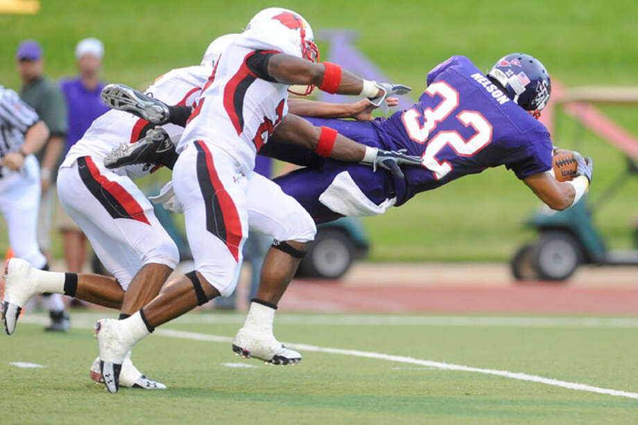 Lamar's Andre Bevil, left, and running back Octavious Logan try to stop SFA defensive back Caleb Nelson, who scores after intercepting Bevil's pass in the first half at Homer Bryce Stadium in University Nacogdoches.  Saturday, September 25, 2010  Valentino Mauricio/The Enterprise / Beaumont