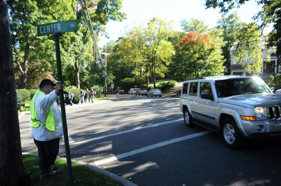 Crossing guard Alan Ritch watches traffic while Greenwich High School students walk home at the intersection of Sound Beach Avenue, Lockwood Road and Center Drive in Old Greenwich, on Wednesday, Oct. 13, 2010. The intersection is a busy one in Old Greenwich.  A resident is lobbying the town to install some traffic control measures to reduce motorists' speed in the area.  Police are compiling accident statistics for the intersection. Photo: Helen Neafsey / Greenwich Time