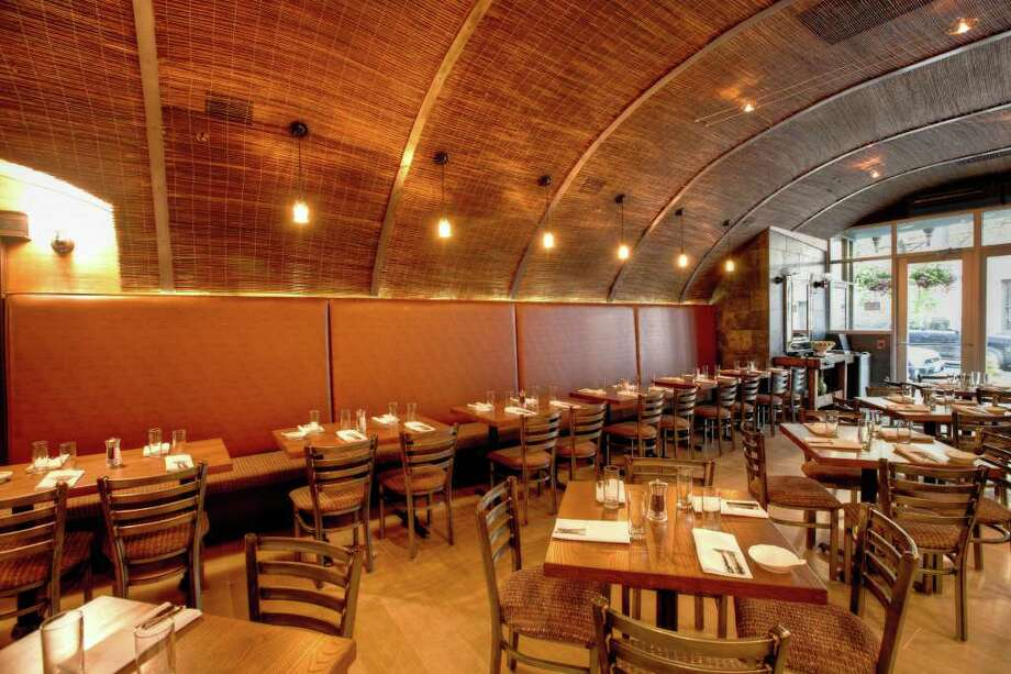 Built as an urban trattoria, Tappo's long narrow space with exposed brick walls, wood floor, deep brown rattan-covered ceiling and a partial wall of large marble tiles, is decorated with large black-and-white prints of scenes of Italy. Photo: Contributed Photo / Stamford Advocate Contributed