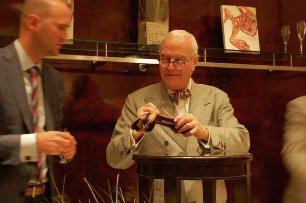 Iconic shoe designer manolo blahnik signs one of his for Shoe designer manolo blahnik
