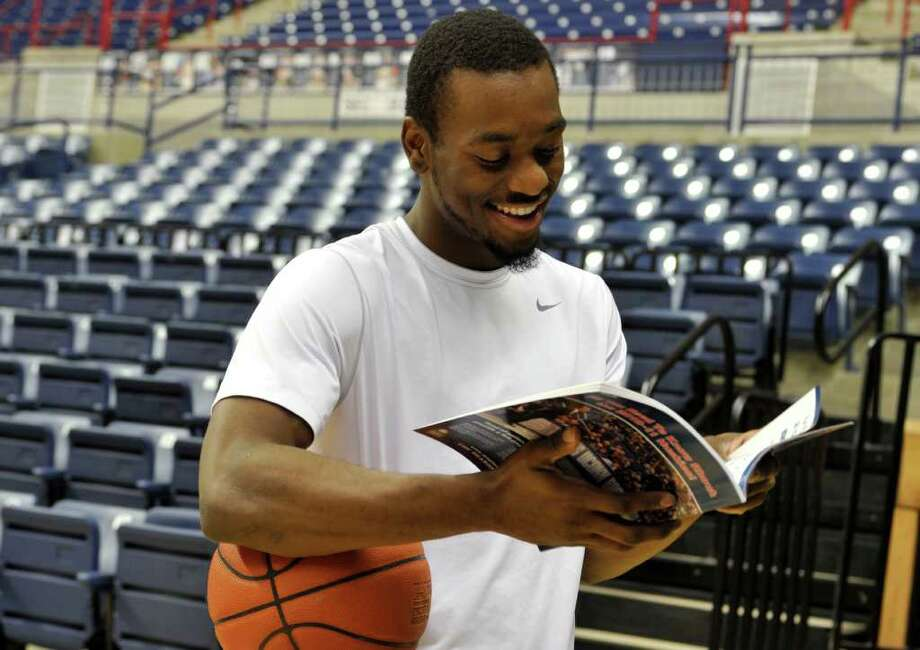 Connecticut basketball player Kemba Walker smiles as he sees his photo in a magazine prior to the Husky Run during the team's media day in Storrs, Conn., Wednesday, Oct. 13, 2010.   (AP Photo/Jessica Hill) Photo: AP