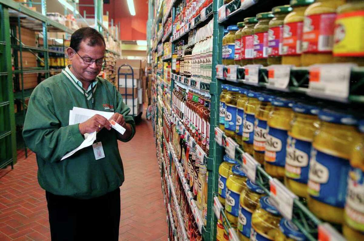 Sribash Ghatak, an employee at Fairway grocery store in Stamford, Conn., is responsible for checking that the UPC code matches all of the 80,000 products in the store He's part of the team of people getting the store ready on Thursday October 14, 2010.