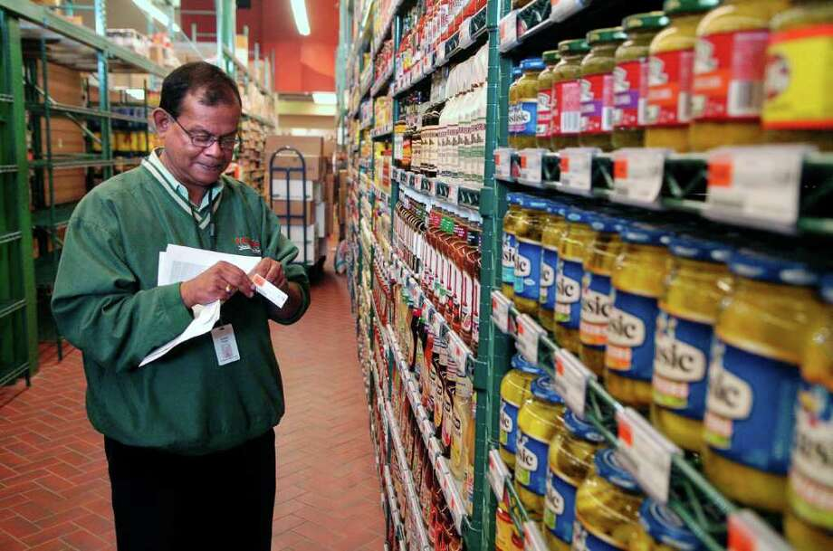Sribash Ghatak, an employee at Fairway grocery store in Stamford, Conn., is responsible for checking that the UPC code matches all of the 80,000 products in the store He's part of the team of people getting the store ready on Thursday October 14, 2010. Photo: Dru Nadler / Stamford Advocate Freelance