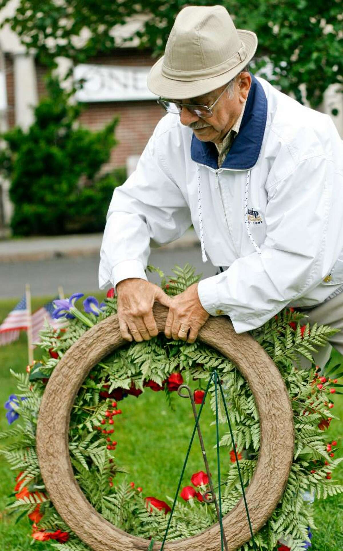Sal Santella places a commemorative wreath on the potential site of a September 11 memorial on the library green in Easton on Friday, Sep. 11, 2009. Flags were also placed on the ground to outline the exact location of the memorial as well as honor those lost during the 2001 attack.