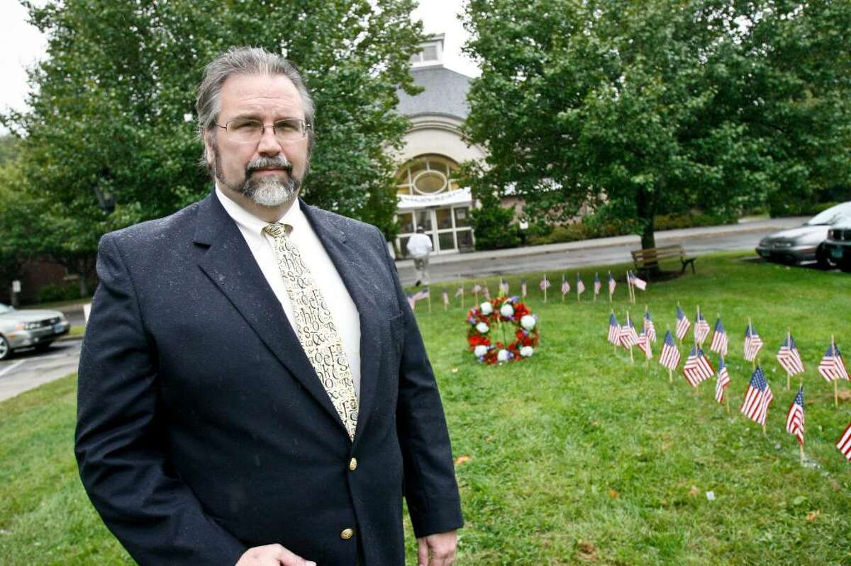 Fairfield architect, Mark Halstead, stands on the potential Easton September 11 memorial location outside the library on Friday, Sep. 11, 2009. Flags and a memorial wreath were placed on the ground to outline the exact location of the memorial as well as commemorate those lost during the 2001 attack.