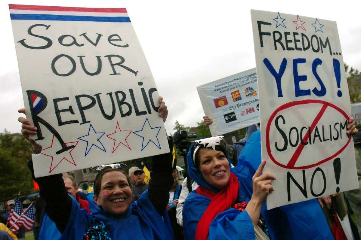 Emily Pepper, left, of Brooklyn, NY, and her sister Bonnie Pepper, of Wallingford, hold up signs during the Tea Party Express rally on Baldwin Plaza, in downtown Bridgeport, Conn. Friday Sept. 11th, 2009.