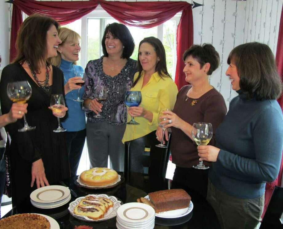 (From left) Dawn Keenan, Diana Loman, Donna Waltzer, Vicki Blumberg, Maria Horvath amd Cecilia Mendoza converse over food and drinks in Waltzer's home. Waltzer may appear on a reality show on The Oprah Winfrey Network, and her friends have pledged to support her while she is filmed for eight weeks. Photo: Vinti Singh / The News-Times