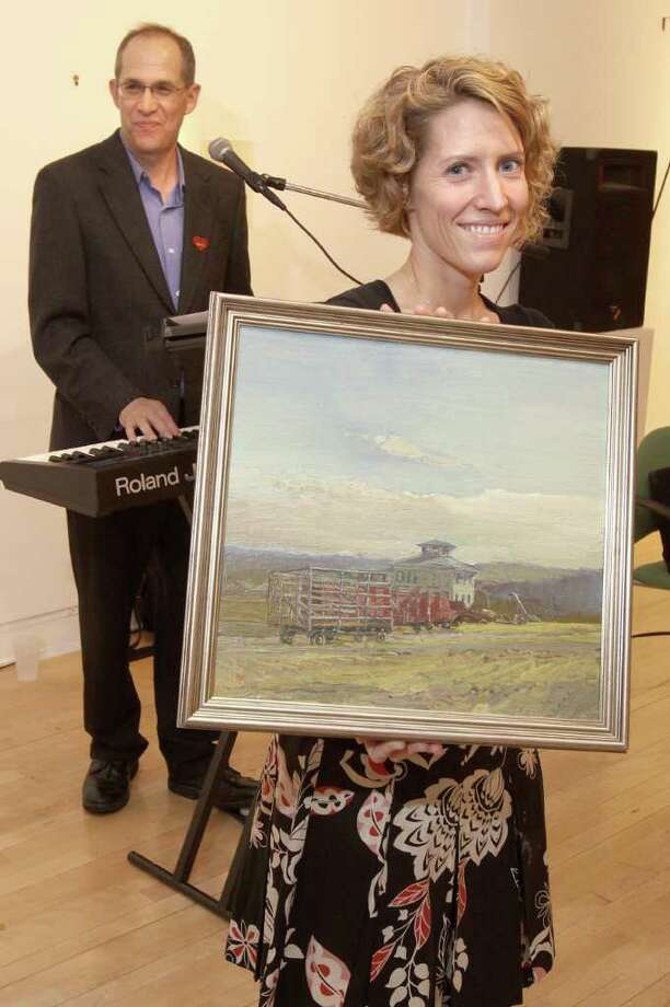 Troy, NY - September 30, 2010 - (Photo by Joe Putrock/Special to the Times Union) - Jenifer Hebner(right) holds a Harry Orlyk Painting while guest auctioneer Richie Philips(left), of WGNA's Sean & Richie Show, tries to drum up live auction bids during the 6th Annual Art Saves Animals, an art auction and reception to benefit the Mohawk & Hudson River Humane Society. Photo: Joe Putrock / Joe Putrock
