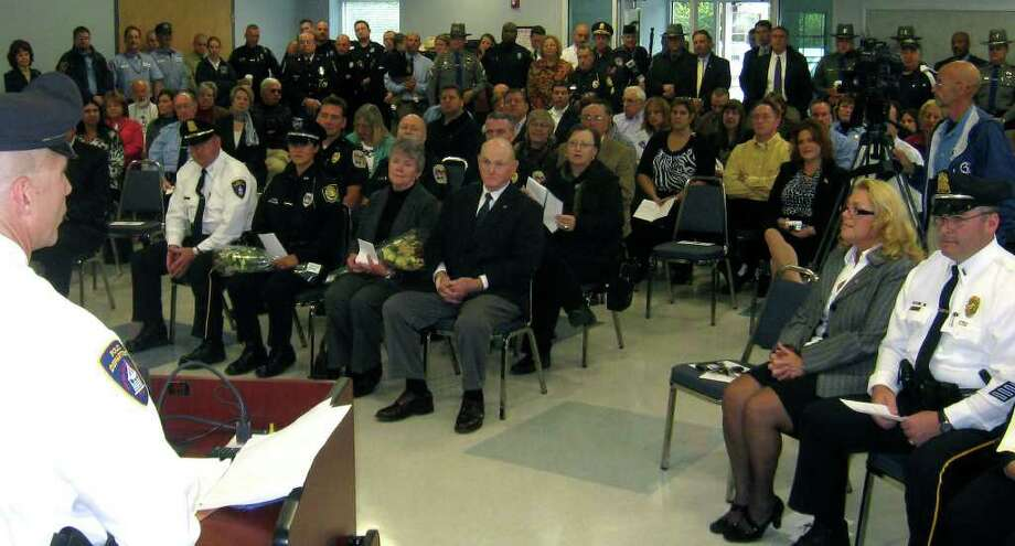 On behalf of outgoing Chief Colin McCormack and the New Milford police department. Lt. James Duda of the New Milford Police Department extends a welcome to new police chief Shawn Boyne during a swearing in ceremony held Friday, Oct. 15, 2010 at the New Milford Community Ambulance barn. Among the crowd of about 160 on hand are, to the right, Mayor Pat Murphy and NMPD Sgt. Mark Buckley. Left-foreground are Chief Boyne, his fiancee, Winsted police Officer Kim Maher, and his parents, Barbara and John Boyne of Lee, Mass. Photo: Norm Cummings / The News-Times