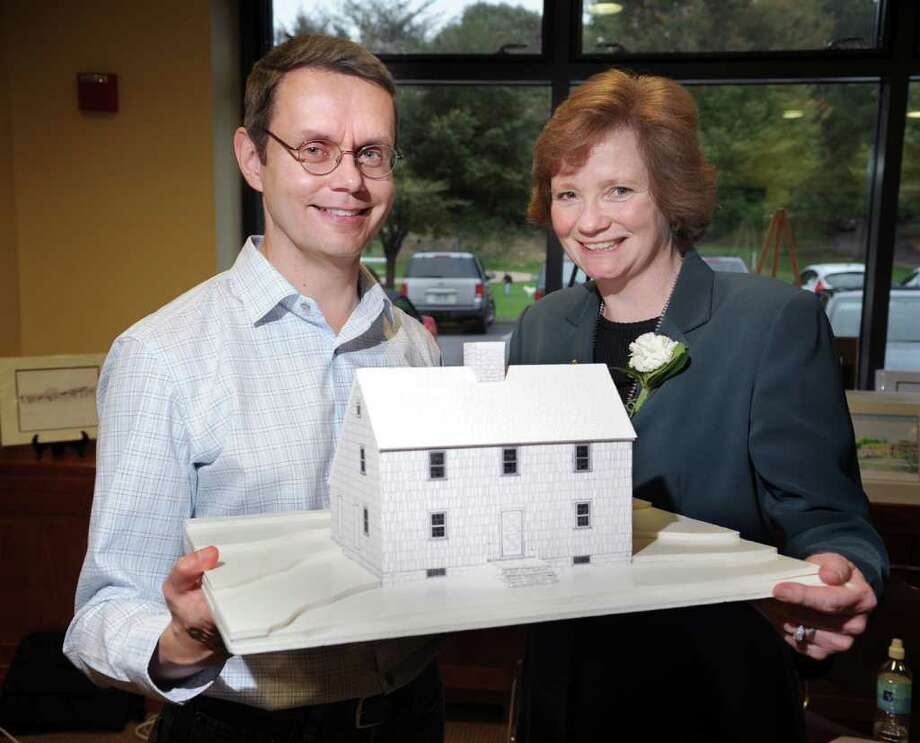Lyon family descendants Charles Boetsch of Warren, Ohio, left, and Julie Pollock of Wasilla, Alaska, right, posed with a scale model of the Thomas Lyon house, the homestead of their ancestors, during a Greenwich Preservation Trust-sponsored gatheing of Lyon members at the Byram Shubert Library, Friday evening, Oct. 15, 2010. Photo: Bob Luckey / Greenwich Time